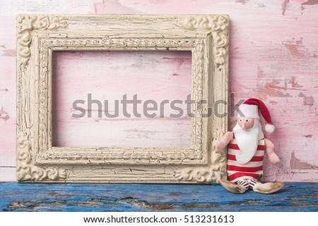 Christmas Santa card, Santa Claus rag doll and empty vintage photo frame on pink wooden background