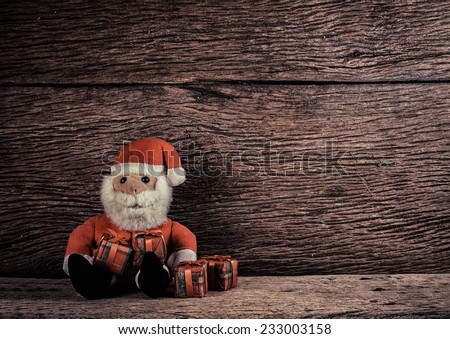 Christmas Santa Claus  and gift box on wooden background  - stock photo