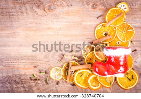 Christmas, Santa Claus boots and Slices of dried orange, lemon, cinnamon, cloves, cardamom. Christmas and New Year decoration frame. Free space for text. - stock photo