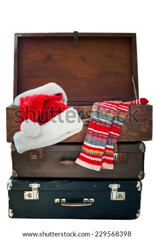 Christmas Santa Claus Caps and Knitting Strips Golfs in Open Wooden Suitcase, isolated on white - stock photo