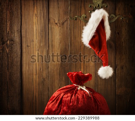 Christmas Santa Claus Hat Hanging On Wood Wall, Xmas Concept, Decoration Over Grunge Wooden Background - stock photo
