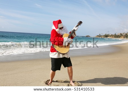 Christmas Santa Claus plays his guitar on the beach.