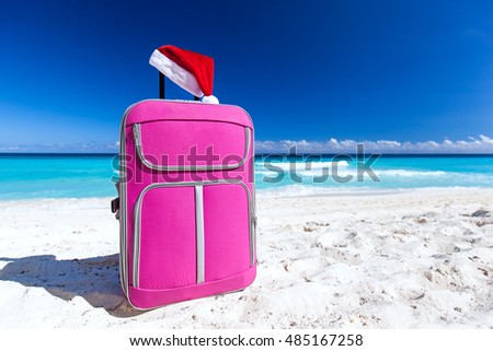 Christmas Santa Claus red hat on handle travel luggage with tropical beach and turquoise sea background. New Year holidays concept
