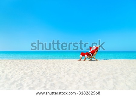 Christmas Santa Claus resting on sunlounger at ocean sandy tropical beach - xmas travel vacation in hot countries concept - stock photo
