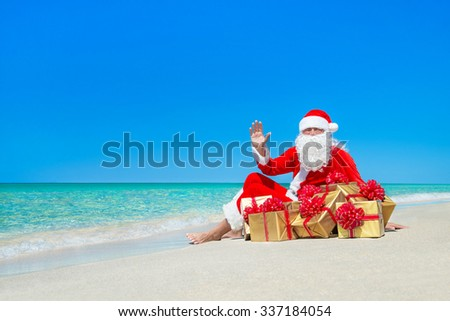 Christmas Santa Claus with gift boxes resting at ocean tropical sandy beach - New year's Day and X-mas travel vacation in hot countries concept - stock photo