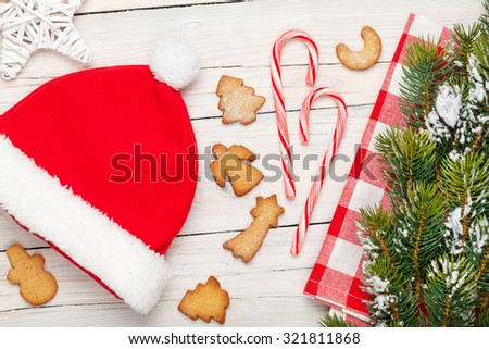 Christmas santa hat, gingerbread cookies and snow fir tree. View from above over white wooden table background - stock photo