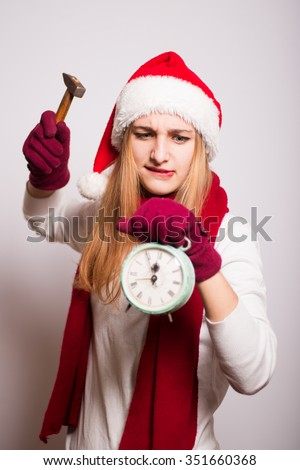 Christmas Santa hat isolated portrait of a girl. She wants to break with a hammer alarm clock on gray background - stock photo