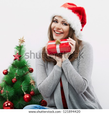 Christmas Santa hat isolated woman portrait hold christmas gift beside green  Christmas Tree. Smiling happy girl seat against white wall.