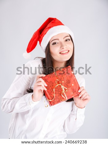 Christmas Santa hat. woman portrait hold christmas gift. Smiling happy girl.christmas, x-mas, winter, happiness concept - smiling woman in sweater and hat with gift box - stock photo