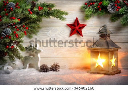 Christmas scene background with a lantern, fir branches, red star, reindeer and snow in front of a bright wooden board with candle light - stock photo