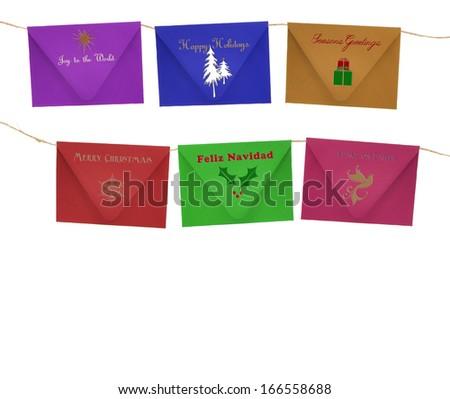 Christmas Season Envelopes (Joy to The World, Seasons Greetings, Happy Holidays, Merry Christmas, Feliz Navidad, Peace on Earth) Hanging on Cord isolated on white background - stock photo