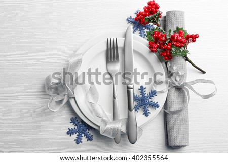 Christmas serving cutlery on plate and napkin over light wooden table - stock photo