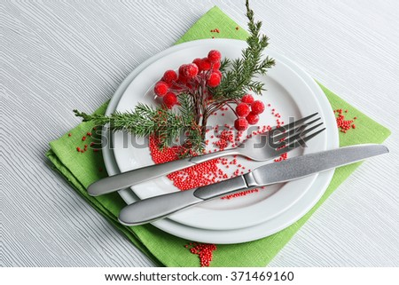 Christmas serving cutlery on plate and napkin over light wooden table, close up - stock photo