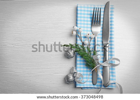 Christmas serving cutlery with a napkin over light wooden table - stock photo