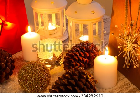 Christmas setting with candles, pine cones, shopping bags and baubles.  - stock photo
