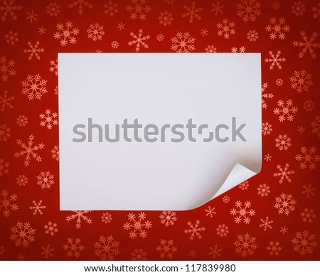 Christmas sheet of curved paper on red snowflakes background - stock photo