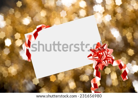 Christmas sheet of paper with bow and ribbons on yellow - stock photo
