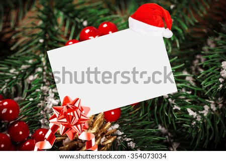 Christmas Sheet Of Paper With Bow And Santa Hat On Beautiful wooden background with snow fir tree. View with copy space