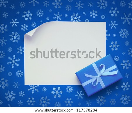 Christmas sheet of paper with small gift on blue snowflakes background - stock photo