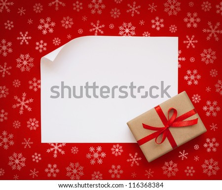 Christmas sheet of paper with small gift on red snowflakes background