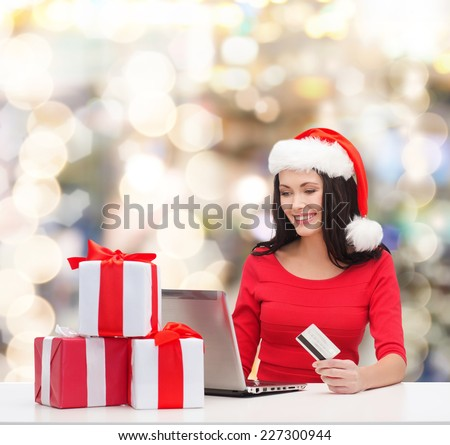 christmas, shopping and people concept - smiling woman in santa helper hat with gift boxes, laptop computer and credit card over lights background - stock photo