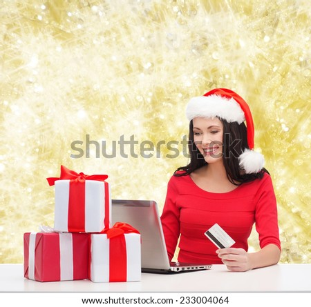 christmas, shopping and people concept - smiling woman in santa helper hat with gift boxes, laptop computer and credit card over yellow lights background - stock photo