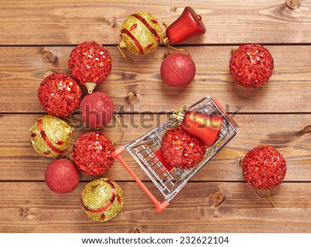 Christmas shopping background compostion of a multiple decoration balls and tiny shopping cart over the wooden surface - stock photo