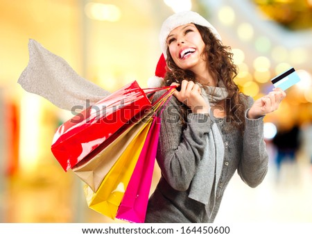 Christmas Shopping. Beautiful Happy Girl With Credit Card and Shopping Bags. Shopping Mall. Shopping Center. Christmas Sales  - stock photo