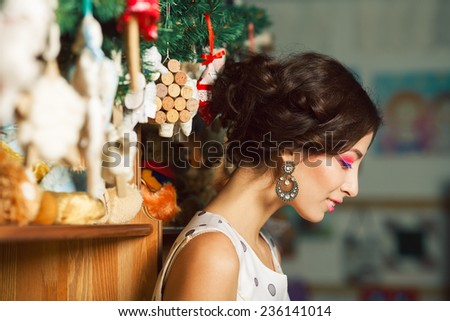 Christmas shopping concept. Emotive portrait of happy beautiful brunette with perfect make-up, hairdo, diamond earrings buying vintage decoration. Close up. Indoor shot - stock photo