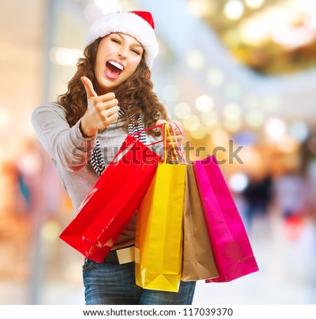 Christmas Shopping. Fashion Girl With Shopping Bags in Shopping Mall showing Thumb up - stock photo