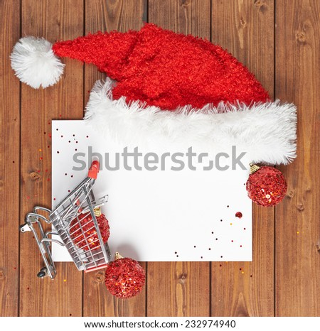 Christmas shopping list composition of the copyspace blank sheet of paper next to the small shopping cart and decorations over the wooden surface - stock photo