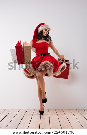 Christmas shopping. Pretty woman jumping with shopping bags against white wall background, wearing red Santa Claus hat and dress - stock photo