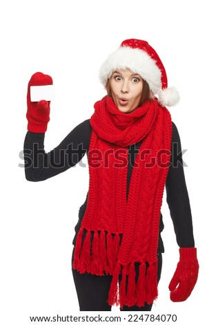 Christmas shopping. Suprised woman wearing santa hat and red scarf and mittens showing blank credit card, over white background - stock photo