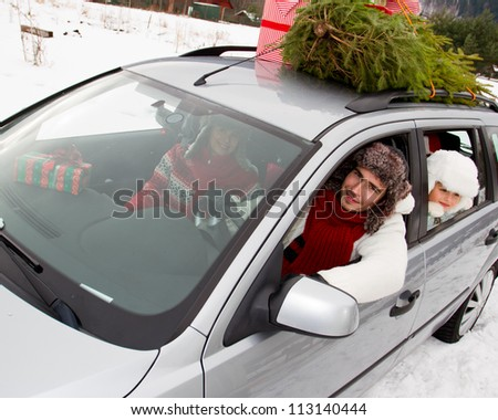 Christmas shopping - the family is riding a car with christmas tree and gifts on the roof of the car - stock photo