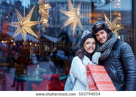 Christmas shopping together. Young happy couple doing christmas shopping. Christmas lights in the background.