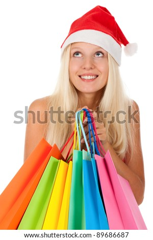 Christmas shopping woman, Happy excited santa girl in red hat and dress, holding colorful bag, looking up to empty copy space, isolated on white background