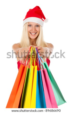 Christmas shopping woman, Happy excited santa girl in red hat and dress, holding colorful bag, looking at camera isolated on white background
