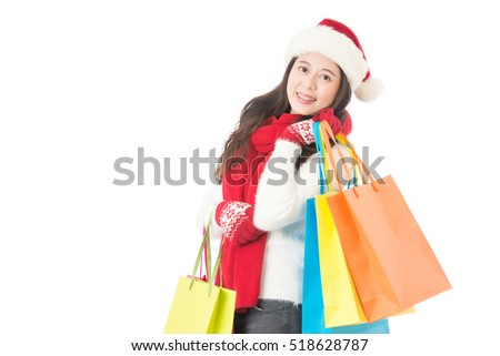 Christmas shopping woman holding shopping bags with gifts. Happy and smiling wearing red santa hat isolated on white background. Mixed race Chinese Asian female model.