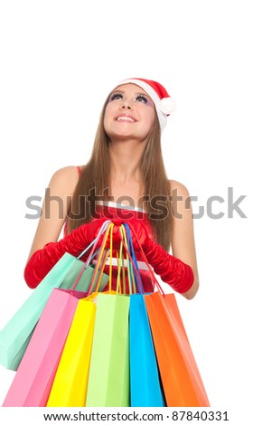 Christmas shopping woman looking up, Happy excited santa girl holding colorful bag isolated on white background
