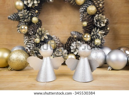 Christmas silver angels on wooden surface with wreath of cones and gold balls on background. - stock photo