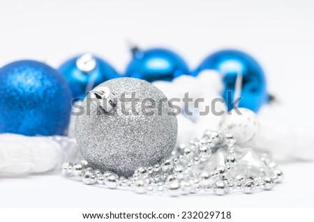 Christmas silver ball in  focus and blue balls in background with ribbons and snow