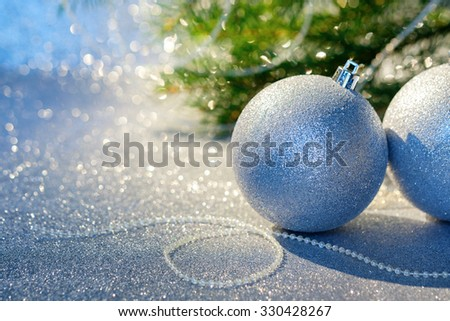 Christmas silver balls on a christmas fir tree background. Selective focus. Space for text.