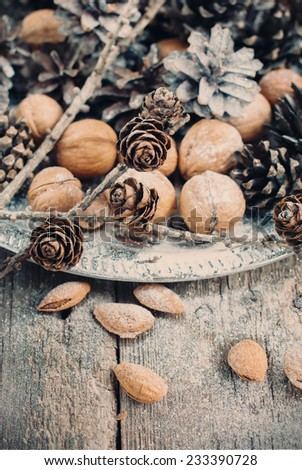 Christmas Silver Tray with Pine cones, Walnuts, Almonds, Nuts on Wooden Background, holiday decoration, toned - stock photo
