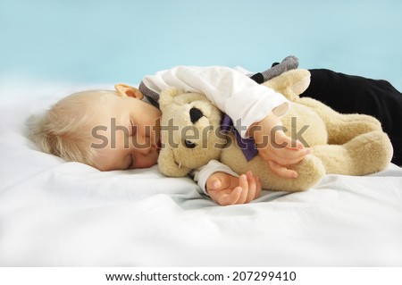 Christmas sleeping newborn baby with teddy bear on blue background. Photo for calendar, card  etc. Baby concept - stock photo