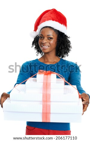 Christmas: Smiling african female with santa hat and holding a pile of presents - stock photo