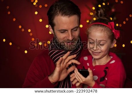 Christmas - smiling father and daughter playing game on mobile phone. Happy family time - modern lifestyle. Christmas tree with lights on dark red as background. - stock photo