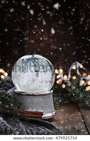 Christmas snow globe with by pine branches, cinnamon sticks and a warm gray scarf with gently falling snow flakes against a rustic background. Shallow depth of field with selective focus on snowglobe.