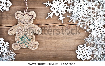 Christmas snowflakes and bear toy on wooden background