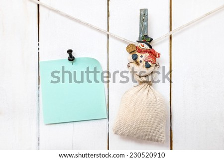 Christmas snowman clothespin hanging on clothesline or rope and holding sack and green blank note paper with push black pin on wood background - stock photo
