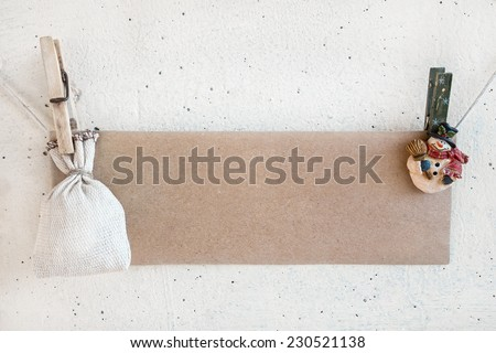 Christmas snowman clothespines hanging on clothesline or rope and holding brown craft paper card and sack on plaster background - stock photo